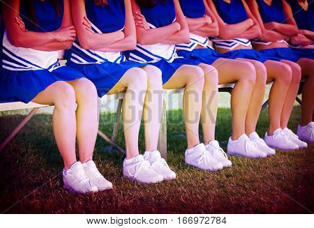 Low section of young cheerleaders sitting with arms crossed on bench in field