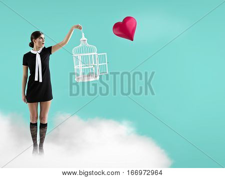 woman standing on cloud with cage captureing flying heart.