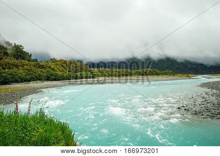 The aqua Whataroa River under clouds in the West Coast on the South Island of New Zealand