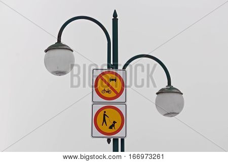 Two restriction signs for motorized vehicles and animals on a lamp post