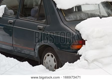 Parked car under snow in a cold winter day