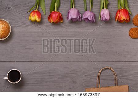 Lilac and red tulips and coffee with biscuits in the lilac wooden table. Banner template layout mockup for Woman Day, Valentines Day and Teacher's Day. Photo for posts, blogs, advertising and news.