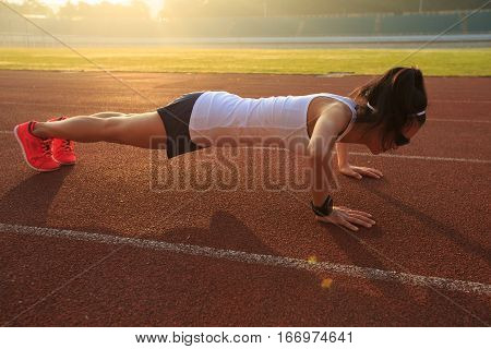 young fitness woman runner doing push ups on stadium track.