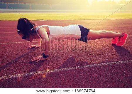 young fitness woman runner doing push ups before run