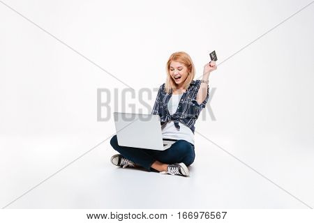 Photo of happy young woman using laptop computer isolated on a white background while holding debit card.