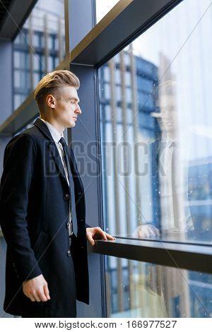 Serious businessman in formalwear standing by window