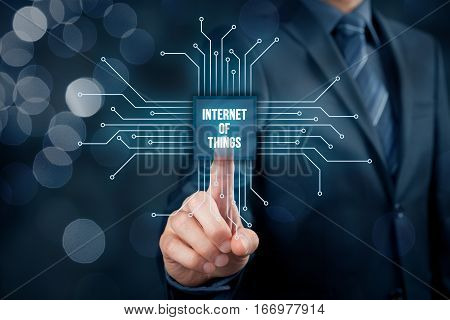 Internet of things (IoT) concept. Businessman click on Internet of Things button in simplified design of chip connected with abstract devices represented by points.