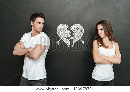 Unhappy young couple standing with arms crossed and looking at each other over background of chalkboard with drawn broken heart