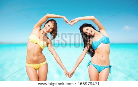 summer holidays, travel, people, love and vacation concept - happy young women in bikinis making heart shape with hands over sea beach background