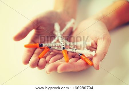 medicine, diabetes, health care and people concept - close up of woman hands holding syringes