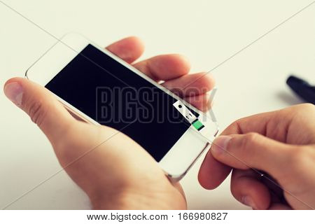 medicine, diabetes, glycemia, health care and people concept - close up of man with smartphone and test stripe checking blood sugar level at home