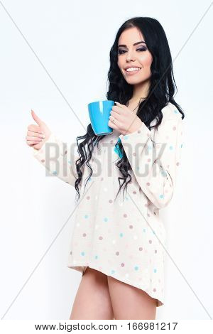pretty woman or cute sexy girl with long brunette hair and smiling face in nightie shirt holds coffee or tea cup shows thumb up isolated on white background