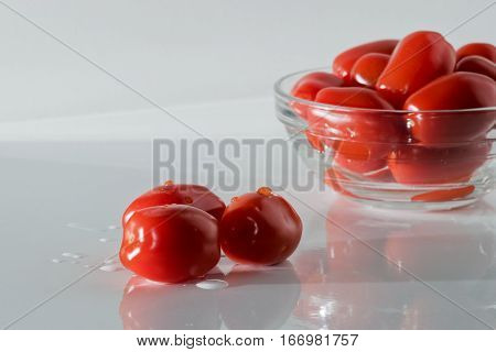 Fresh red cherry tomatoes closeup on white table.