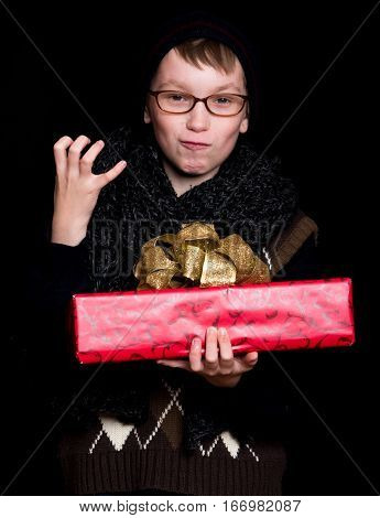 small smiling boy or cute nerd kid in glasses hat and fashionable knitted scarf on black background holds red present box with golden bow