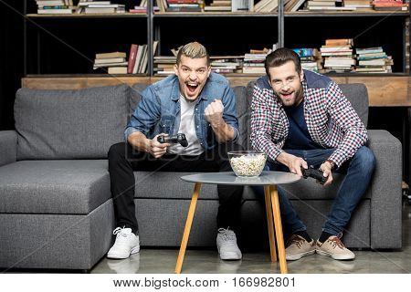 Excited young men playing with joysticks on couch