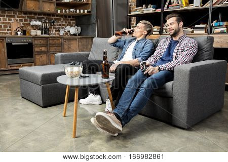 Young male friends sitting on couch and drinking beer while playing with joystick
