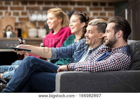 Young male and female friends sitting on couch and watching tv