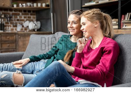 Young smiling women sitting on couch together