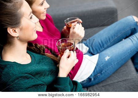 Smiling young women sitting on couch and drinking tea