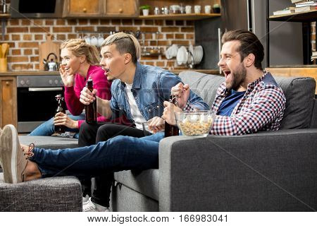 Excited male and female friends drinking beer and eating popcorn on couch