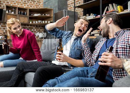 Excited young friends drinking beer and giving high five at home