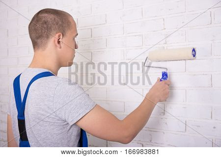 Back View Of Man Painter In Workwear Painting Wall With Paint Roller