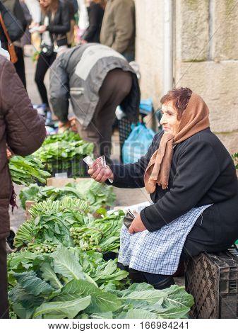 Santiago de Compostela Spain - December 14 2013 - Old woman selling grelos (greens) in the Abastos Market in Santiago de Compostela