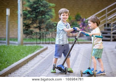 Two Cute Boys, Compete In Riding Scooters, Outdoor In The Park,