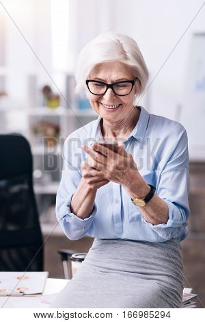 Getting acquainted with new gadget. Charismatic smiling aged woman standing in the office and holding the mobile while expressing interest and joy