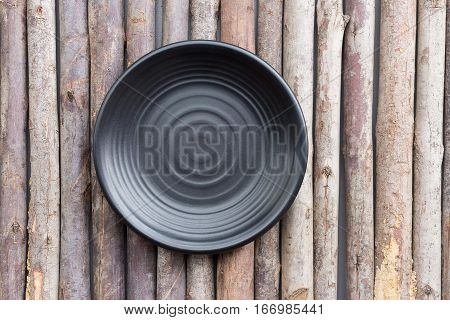 Black plate on a wooden floor, black dish empty for kitchen background.