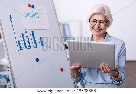 Creating the project. Glad positive aged businesswoman standing near the white board in the office and holding the laptop while smiling and working