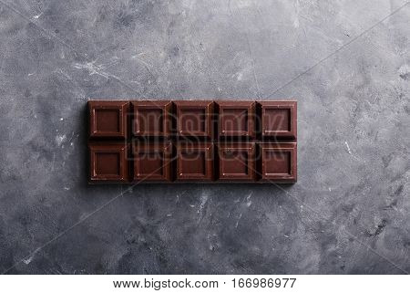 A large bar of chocolate on gray abstract background. Background with chocolate. Chocolate. Sweets