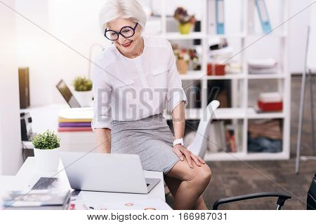 Happy working hours. Smiling cheerful aged business lady sitting on the table in the office and using the laptop while working and expressing creativity