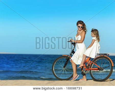 mother and daughter riding a bike  on the beach