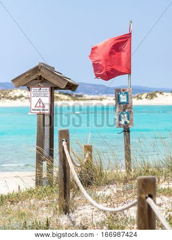 Red flag on Ses illetes beach Formentera (text translation: Do not cross)