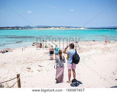 Formentera Spain - May 25 2015: View of the firsts tourists in Ses Illetes beach looking for a place on the beach Formentera Spain.