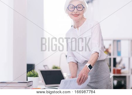 My working routine. Delighted cheerful glad businesswoman standing near the table in the office and holding papers while smiling and looking at the audience