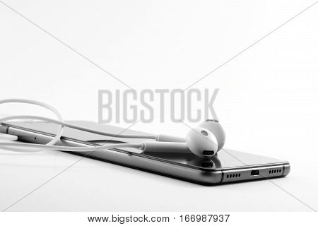 Mobile phone black and white headphones on a light background