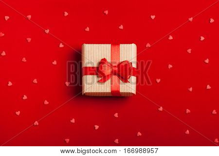 A gift in kraft box with a red bow on a red background with hearts. Surprise your loved one. The concept of the day of St. Valentine's, weddings, engagements, Mother's Day, birthday, New Year, Christmas and other holidays. Flat fly