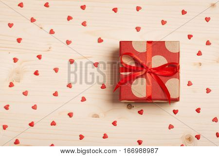 A gift in red box with a bow on a wooden background with hearts. Surprise your loved one. The concept of the day of St. Valentine's, weddings, engagements, Mother's Day, birthday, New Year, Christmas and other holidays. Flat fly
