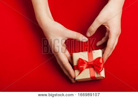 Hands holding gift in kraft box with a bow on a red background.Surprise your loved one. The concept of the day of St. Valentine's, weddings, engagements, Mother's Day, birthday, New Year, Christmas and other holidays. Flat fly. Place for text