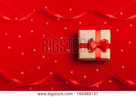 A gift in kraft box with a red bow and ribbons on a red background with hearts. Surprise your loved one. The concept of the day of St. Valentine's, weddings, Mother's Day, birthday, New Year, Christmas and other holidays. Flat fly. Place for text