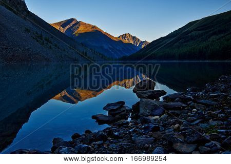 Altai, the North-Chuya ridge - Highlands region of Siberia. Sunset sky and peaks reflecting in the water