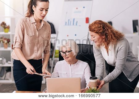 Owner of the company. Cheerful glad charming businesswoman sitting in the office in front of the laptop and typing while her subordinates standing and holding clipboard and cup of tea
