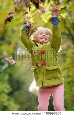 Little blonde girl tossing dried leaves in air