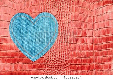 Heart made of denim lies on the red crocodile skin. View from above
