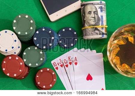 10 to Ace heart straight flush on poker and casino chips money on green table