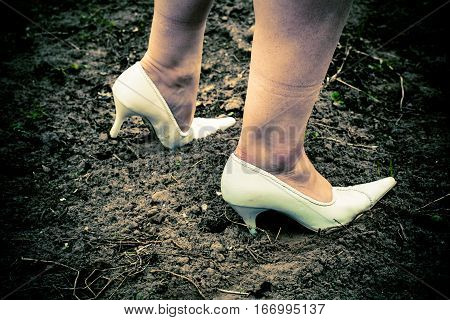 A girl walks on the dirty ground. On her feet are shod with white wedding shoes.