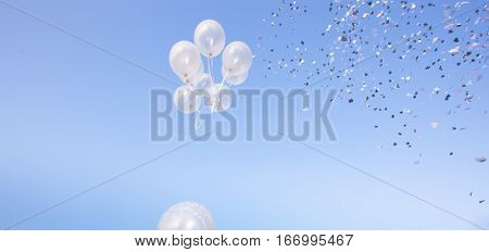 ballons against blue sky with confetti at celebration