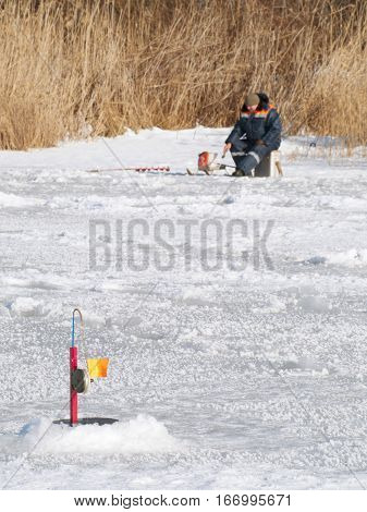 Fisherman on the lake ice fishing rod and ice fishing